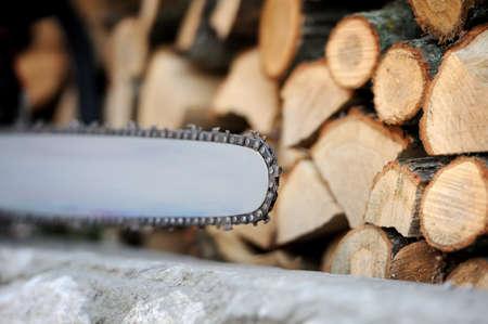 Motosierra primer plano y muchos troncos de árboles Foto de archivo - 45339907