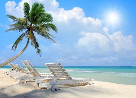 Tropical beach with a sun-lounger facing the blue sea