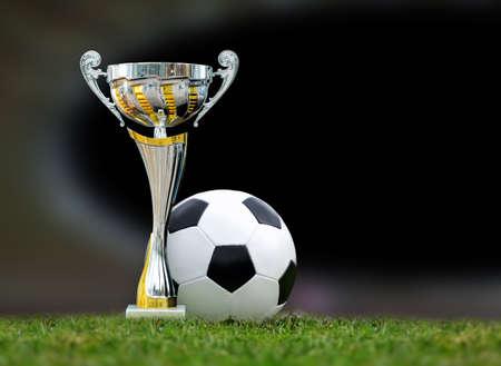Close golden soccer trophy and ball in green stadium grass Banco de Imagens