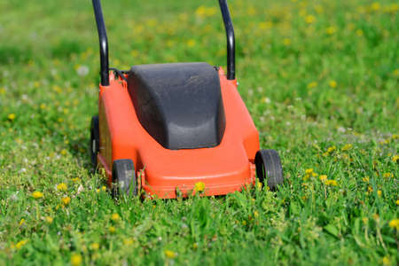 grass cutting: Orange Lawn mower cutting grass. Gardening concept background Stock Photo
