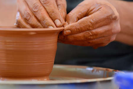 Hands of a potter. Potter making ceramic pot on the pottery wheel Reklamní fotografie