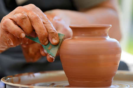 Hands of a potter. Potter making ceramic pot on the pottery wheel Stock Photo