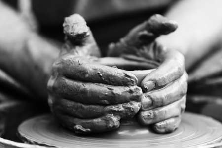 Hands of a potter. Potter making ceramic pot on the pottery wheel Фото со стока
