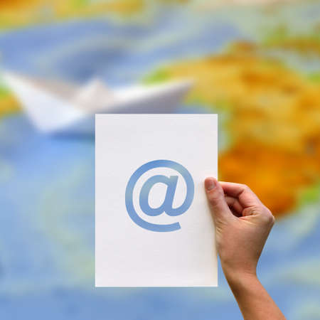Female hand holding paper blank with email network communication perforated paper at sign