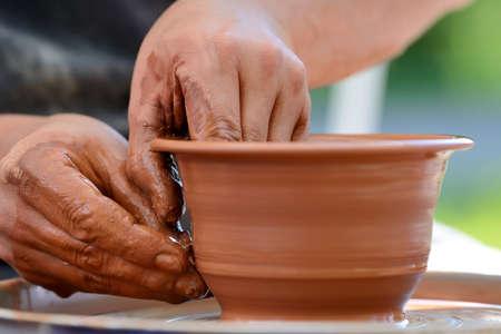 Hands of a potter. Potter making ceramic pot on the pottery wheel Lizenzfreie Bilder