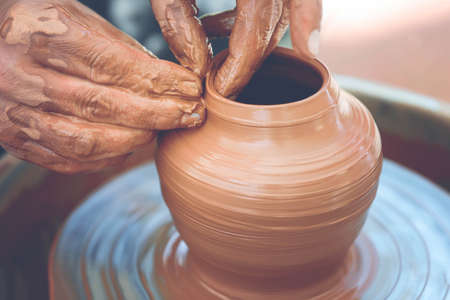Hands of a potter. Potter making ceramic pot on the pottery wheel 스톡 콘텐츠