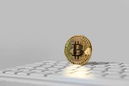 Bitcoin gold coin on white keyboard