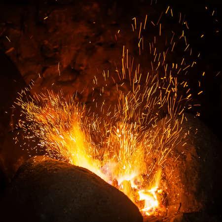 Des étincelles rouges brûlantes volent d'un grand feu. Abstrait sombre