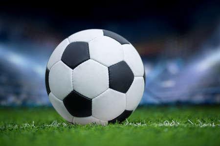 Closeup soccer ball in green grass on stadium