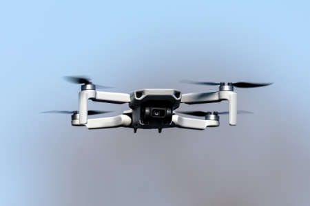 Drone Quadcopter during flight on a sunny day on blue sky background Stock Photo