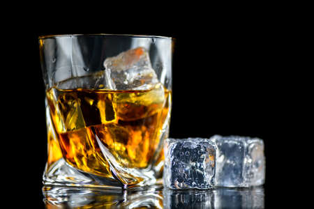 Glass of whiskey or other alcohol with cube ice on black background
