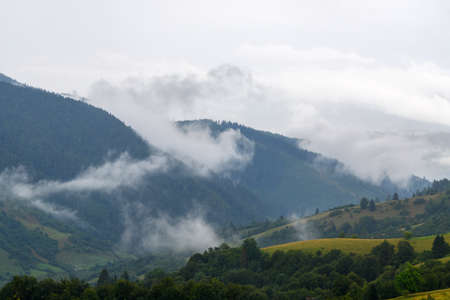 Majestic view on beautiful fog and cloud mountains in mist landscape. Summer time after rain