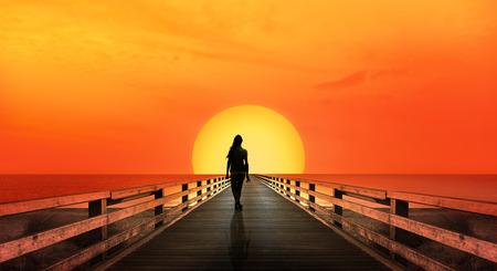 Woman walking into sunset