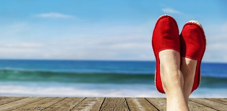 Legs with red cloth shoes in front of beach and sea