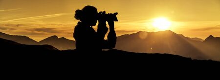 Photographer at sunrise in the mountains Silhouette Фото со стока