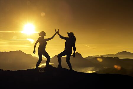 Two women high five on a mountaintop Silhouette