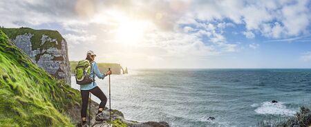 Woman with backpack hiking at coastal trail in Normandie Panoramic View
