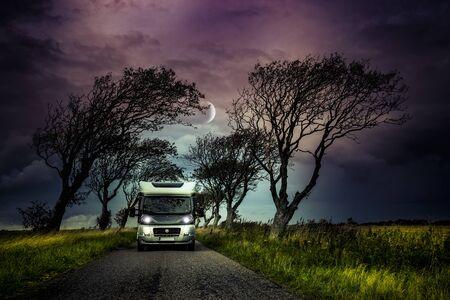 Mobile home in a tree avenue at twilight Reklamní fotografie