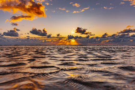 Beautiful sunset at the sea with clouds and water reflection