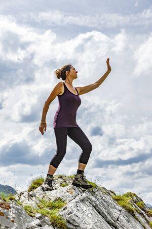 Female posing in winner pose on a mountain summit Foto de archivo - 131335581