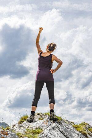 Female posing in winner pose on a mountain summit Foto de archivo - 131335585