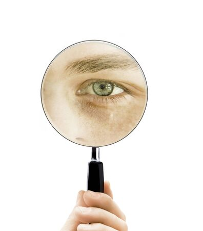 Young man looks through a magnifying glass Banque d'images
