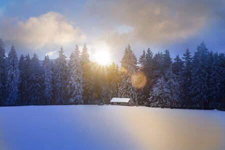 Log cabin window in wintry forest at sunrise Stock Photo
