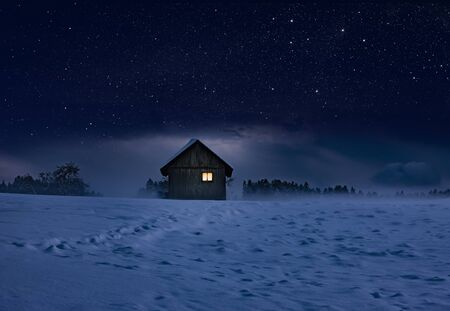 Illuminated log cabin in winter night