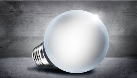 Glowing light bulb on gray background with bokeh effect