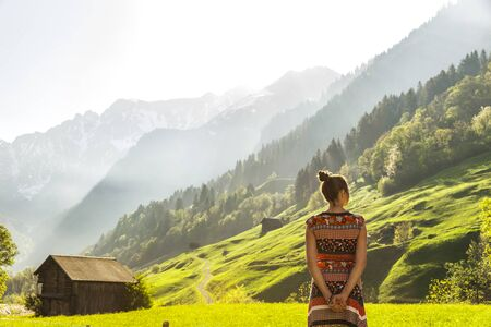 Woman with colorful dress in Swiss mountain landscape