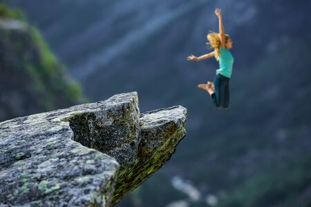 Happy woman jumping from a rock