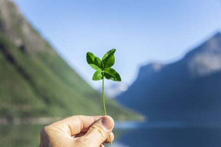 Four-leaf clover in one hand against a fjord landscape, Norway Stock Photo