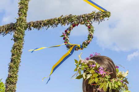 With floral wreath on midsummer tree in Sweden