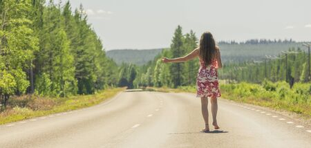 Woman hitchhiking at a country road in sweden