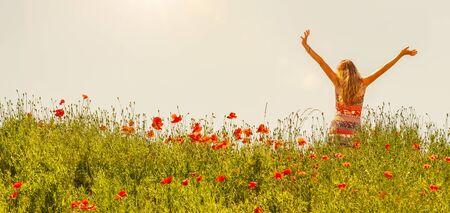 Happy woman wearing summer dress in poppy field