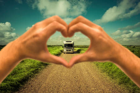 Motorhome on a dust road seen through a heart hand Zdjęcie Seryjne