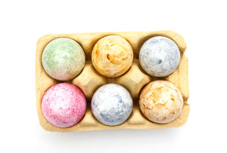 Brightly colored Easter eggs in an egg carton isolated on a white background Zdjęcie Seryjne