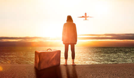 Young woman with a suitcase at sunset
