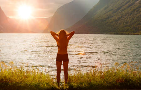 Happy woman on the bank of a mountain lake at sunrise