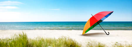 Colorful parasol on the beach by the sea Фото со стока