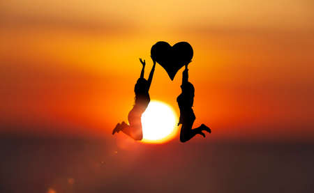 Two women jump with a heart in front of the sun disk 스톡 콘텐츠