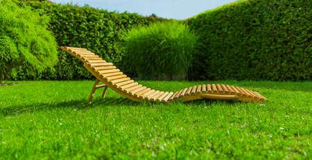 Wooden sun lounger in a garden