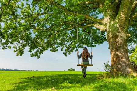 Woman on a swing by an oak tree