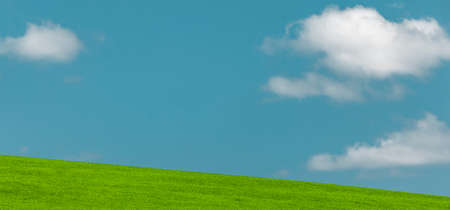 White clouds and blue sky with a meadow 스톡 콘텐츠