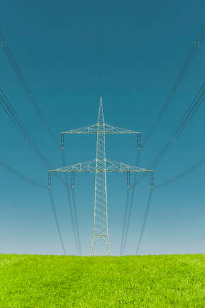 High voltage pylon on a green meadow