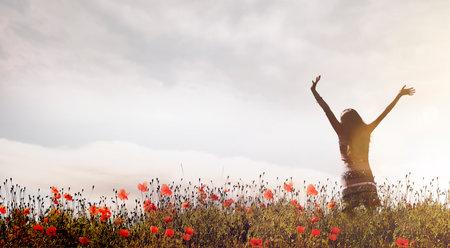 Happy woman in a poppy field 스톡 콘텐츠