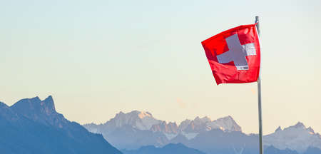 Swiss flag in front of alpine panorama in the high mountains 스톡 콘텐츠