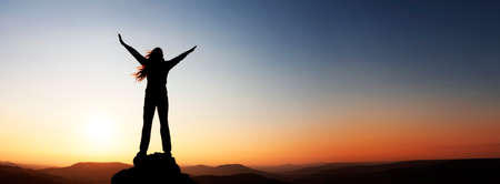 Woman with arms raised over the horizon at sunset