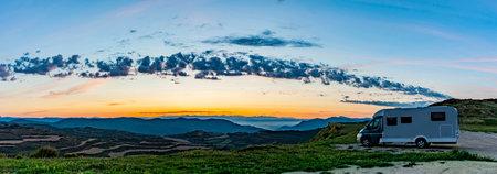 Camper on a hill at sunrise
