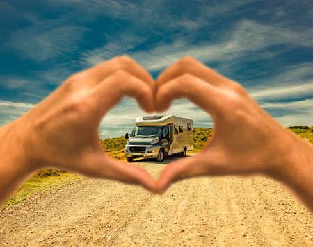 Recreational vehicle on a dust road seen through a heart hand